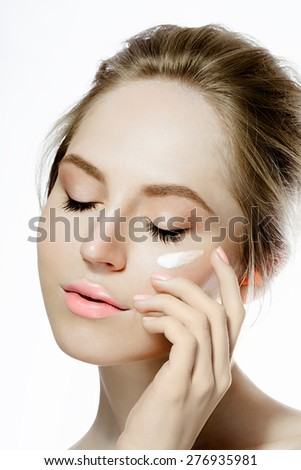 Beauty woman applying cream on the face - stock photo