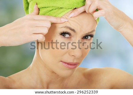 Beauty woman checking wrinkles on her forehead, closeup - stock photo