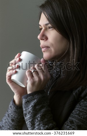 Beauty woman drinking tea while she's looking trough a window