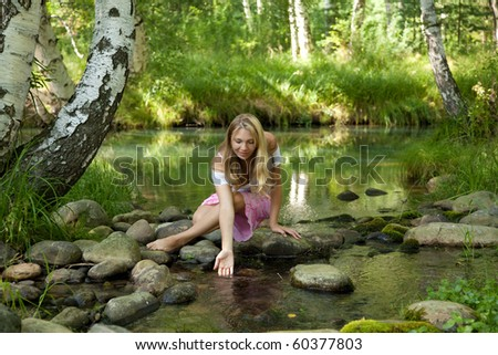 beauty woman drinks water out creek at summer