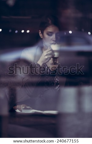 Beauty woman enjoying cup of hot beverage.Beautiful smiling young woman drinking coffee in cafe.Businesswoman working on laptop enjoys coffee,muffins and croissant.Image toned, noise added. - stock photo