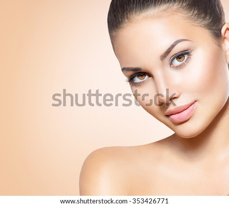 Beauty Woman Face closeup. Beautiful brunette young spa model girl with perfect skin. Skin care concept. Fresh Clean Skin. Portrait of female looking at camera and smiling. Beige background