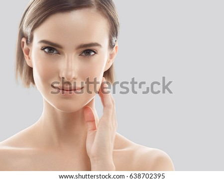 Beauty Woman face Portrait. Beautiful model Girl with Perfect Fresh Clean Skin. Blonde short hair Youth and Skin Care Concept. Isolated on a gray background