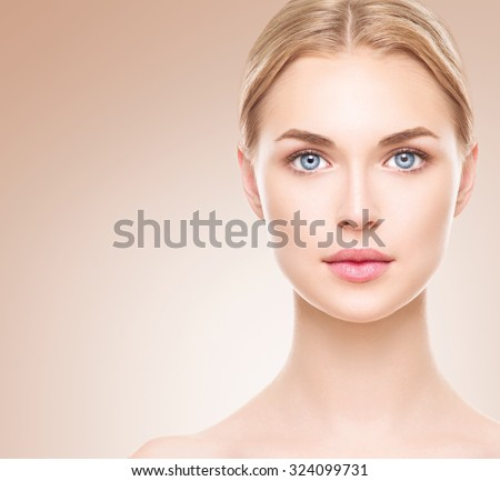 Beauty Woman face Portrait. Beautiful Spa model Girl with Perfect Fresh Clean Skin. Blonde female looking at camera and smiling. Youth and Skin Care Concept. Over beige background