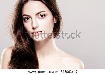 Beauty Woman face Portrait. Beautiful Spa model Girl with Perfect Fresh Clean Skin. Brunette female looking at camera and smiling. Youth and Skin Care Concept. Over beige background - stock photo