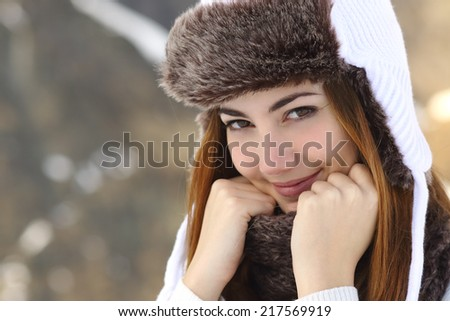 Beauty woman face portrait warmly clothed in winter holding a scarf outdoors - stock photo