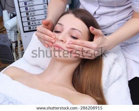 Beauty woman having cosmetic massage, facial treatment, close up. - stock photo