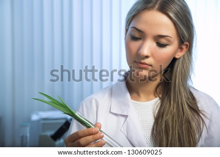 beauty woman holding green plant in laboratory tube