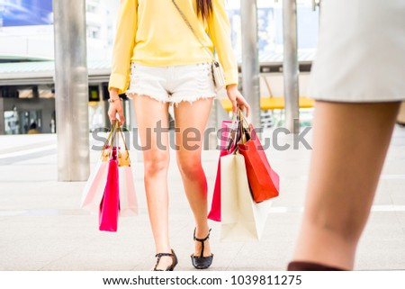 Beauty woman holding many shopping bags and walking on street in city in fashion boutique.