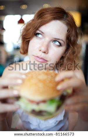 beauty woman in cafe eating hamburger