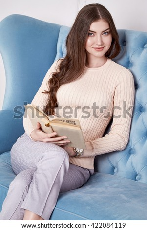 Beauty woman in perfect home interior comfort furniture flower candle girl wear casual fashion wool sweater style pants and shoes clothes for office walk date natural makeup and sexy body book