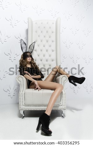 Beauty woman on chair in bunny mask - stock photo