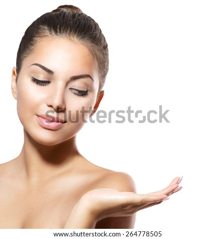 Beauty Woman Portrait. Beautiful Spa Girl showing empty copy space on the open hand palm for text. Proposing a product. Gestures for advertisement. Isolated. Fresh Clean Skin. Skin Care Concept - stock photo