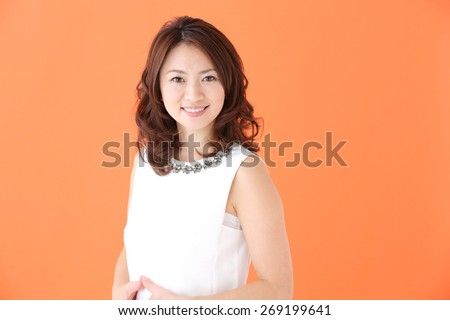 Beauty Woman Portrait. Healthy Long Curly Hair. Beautiful Young Woman isolated on a orange background