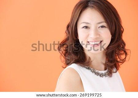 Beauty Woman Portrait. Healthy Long Curly Hair. Beautiful Young Woman isolated on a orange background - stock photo