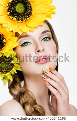 Beauty Woman Portrait. Professional Makeup and Manicure. Fashion model with hairstyle and sunflowers in her hair. Summer Time - stock photo