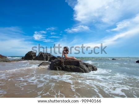 Beauty woman sitting on rock in amazing tropical ocean - stock photo