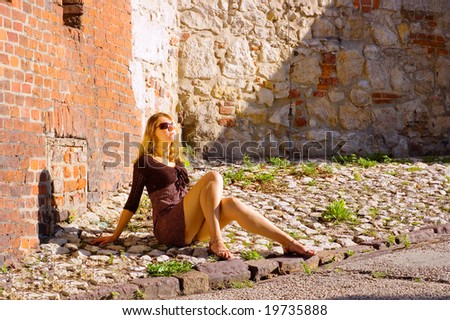 Beauty woman sitting under the sunlight in a sunglasses - stock photo