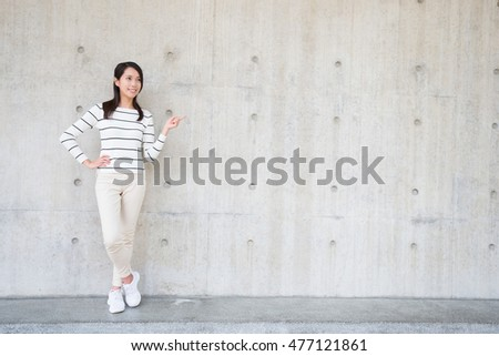 beauty woman smile and show something to you with white wall, asian