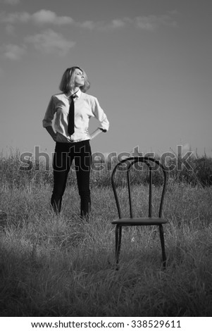 Beauty woman standing at the field and looking in expanse  - stock photo