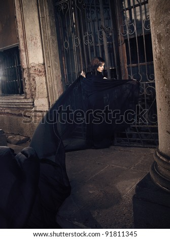 Beauty woman standing in front of old doors to castle with black fabric