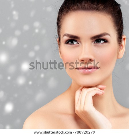Beauty Woman Winter Snow face Portrait. Beautiful Spa model Girl with Perfect Fresh Clean Skin female smiling over gray background. Beautiful hairstyle Youth and Skin Care Concept. Studio shot.