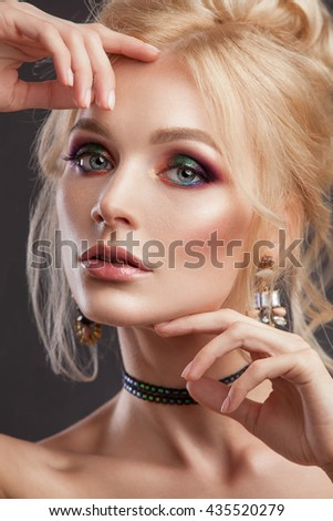 Beauty woman with beautiful make-up color . Blond hair , raised hair , jewelry on his neck , clean skin , beautiful face . Portrait shot in studio on a dark background .
