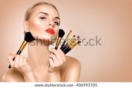 Beauty Woman with Makeup Brushes. Natural Make-up for Blonde Model Girl with Blue Eyes. Beautiful Face. Perfect Skin. Applying Holiday Makeup, orange color lipstick and manicure over beige background - stock photo