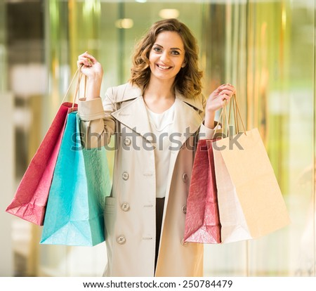 Beauty woman with shopping bags in shopping mall is looking at the camera. Sales. Shopping Center. - stock photo