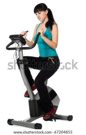 beauty woman working out with stationary bicycle - stock photo