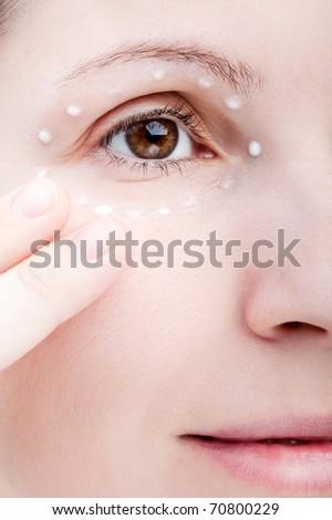 Beauty women applying female eye skin makeup cream - stock photo