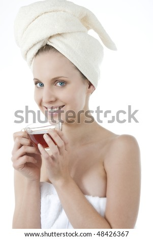 Beauty wrapped in towel with herbal tea