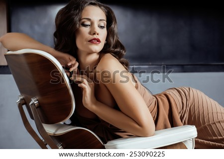 beauty yong brunette woman sitting near fireplace at home, winter warm evening in interior, waiting to celebrate - stock photo
