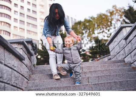 Beauty young asian woman mom with freckles and her son relaxing outdoors. Mother with dark hair and her son is blond. Unusual appearance and heredity concept. Mom helping her son go down the ladder - stock photo