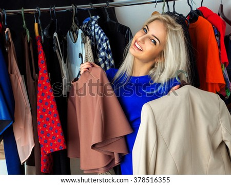 Beauty young blonde girl smiling in clothing store. Happy young lady with a lot of clothes. Shopping concept. - stock photo
