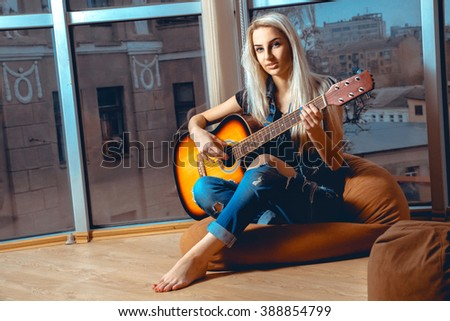 Beauty young blonde lady plays guitar. Girl with guitar. Woman playing guitar. leisure with guitar. - stock photo