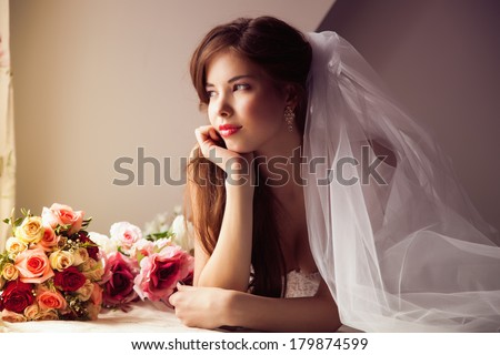 Beauty young bride looking out the window - stock photo