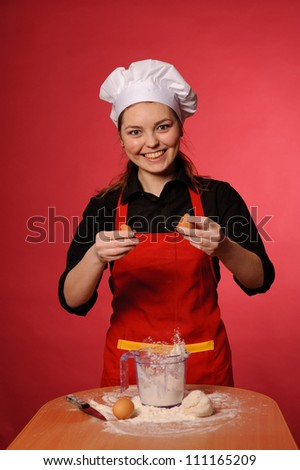 beauty young cook make bread or cake and break egg - stock photo