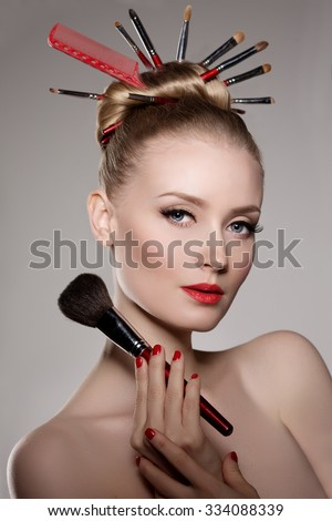 Beauty young girl model stylist with brushes in volume hairstyle. Woman with bright luxurious makeup, long eyelashes with mascara, neat manicure, red lipstick - stock photo