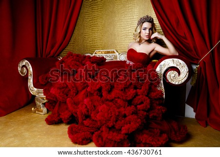 beauty young queen long blond hair crown on her head  sitting on sofa