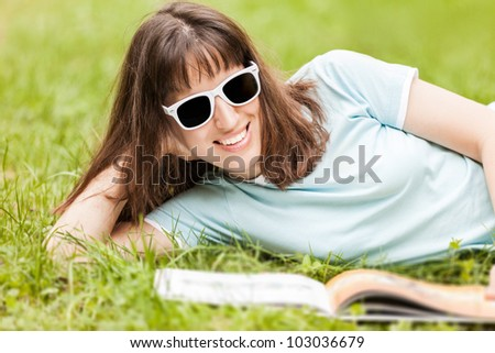 Beauty young smiling caucasian woman in sunglasses reading book outdoor on green grass field - stock photo