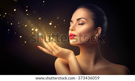 Beauty Young Woman Blowing Magic Dust with golden hearts and stars from her hands. Valentine's Day Holiday Concept. Isolated on black background Beautiful Romantic Girl. Miracle, magic of love - stock photo