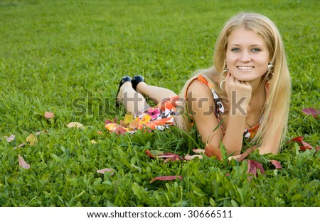 Beauty young woman lying on a green grass
