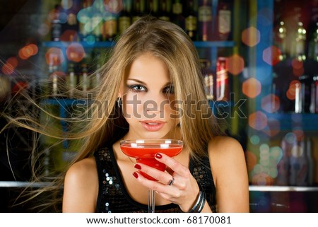 Beauty young woman portrait with a glass drinking a cocktail at a bar - stock photo