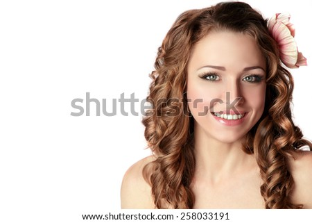 Beauty Young Woman Smile. Perfect Skin, Natural Fresh Make-up. Happy Smiling Girl Face. Long Curly Hair with Flower. Isolated on White. Gorgeous Woman. - stock photo