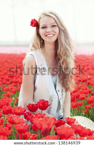 beauty young woman with hat in her hands on the meadow with red flowers tulips, outdoors