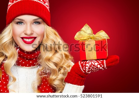 Beautyful blond woman with christmas box gift on red background.