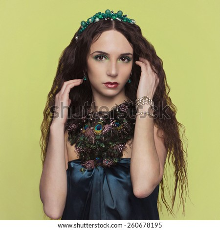 beautyful brunette young woman with accesories.fashionable girl.jewelery.plumage - stock photo