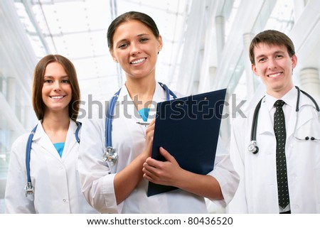 Beautyful young female doctor standing in front of his team and smiling - stock photo