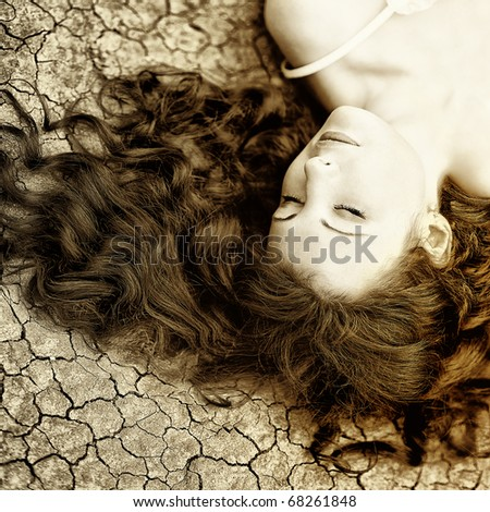 Beauutiful young woman with long hair on the dried up ground - stock photo